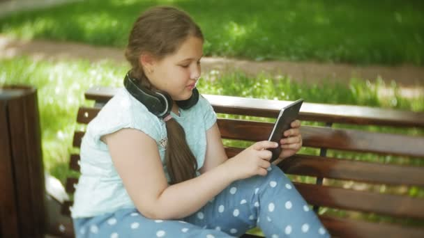Little fat girl with a tablet PC and headphones sitting on a bench listening to music or watching a video in a summer park