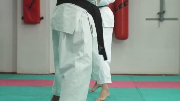 Egy fiatal ember, izmos test, és egy nő gyakorló harcművészetek Goju-Ryu Karate-Do