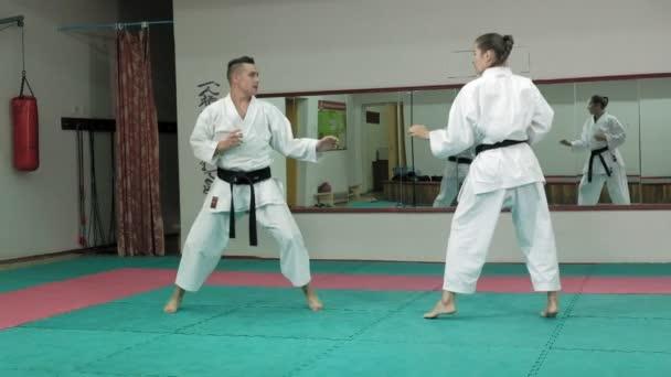 Egy fiatal ember, izmos test, és egy nő gyakorló harcművészetek Goju-Ryu Karate-Do szuper lassú mozgás