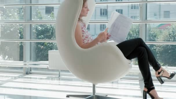 attractive businesswoman sitting on a white chair in a glass office and checks documents