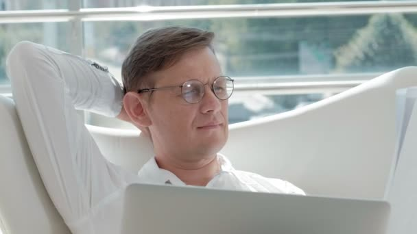 Mature businessman sitting on a white chair in a glass office and working on a laptop