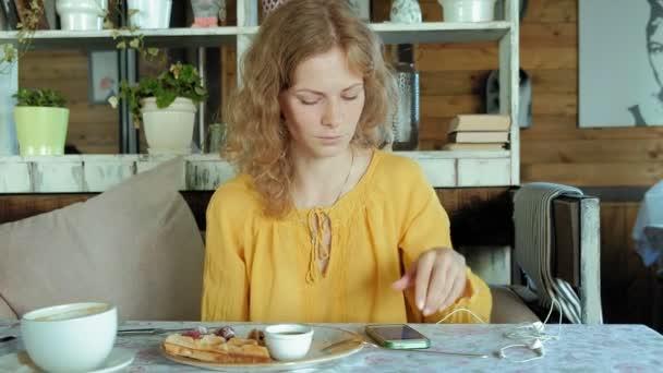 Krásná žena jí vafle v kavárně 4k