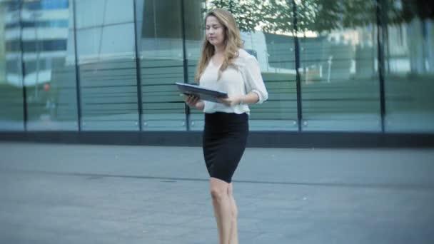 Mladá podnikatelka je procházka v parku obchodního centra