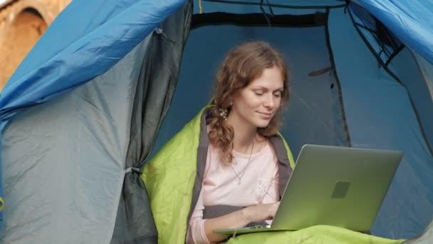 Mladá žena, pracující za notebook v turistické stanu nedaleko starého mostu