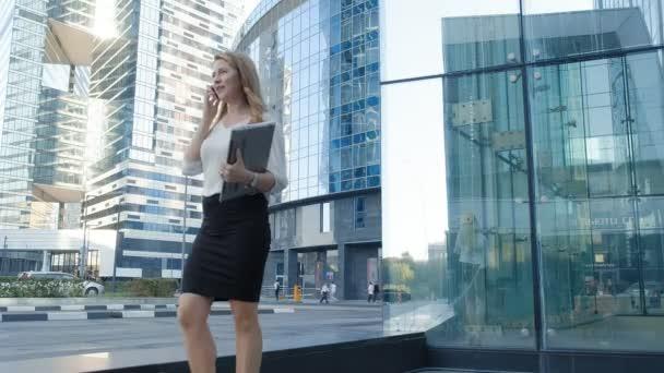 Mladé ženy mluví používá smartphone v city parku business center