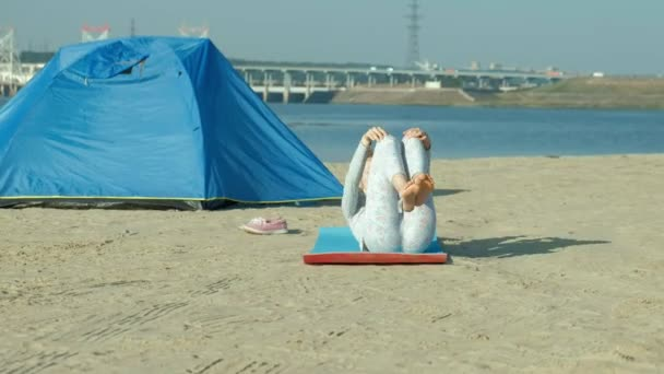Beautiful woman doing yoga at sea, harmony and freedom, background from sea and sand blue tourist tent, concept of yoga and peace during holidays