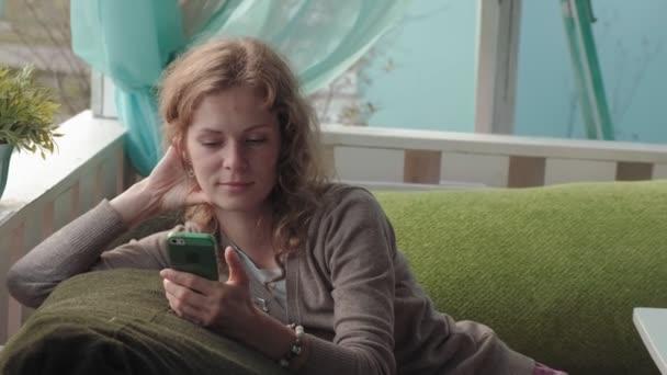 Žena s používáním aplikace na smartphone v café usmívá a textových zpráv na mobilním telefonu. Krásné multikulturní mladé příležitostné ženské profesionální na mobilním telefonu 4k