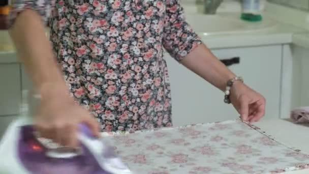 žena žehlení hory prádla doma v kuchyni