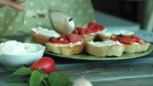 Close-up shot of a womans hand is prepared from bread cheese and vegetables for an Italian bruschetta.