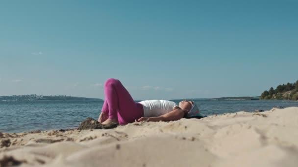 Régi nyugdíjas asszony csinál néhány jóga a strandon