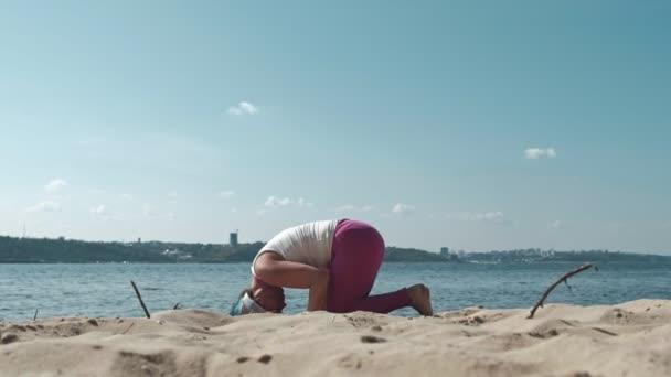 Starý vysloužilý žena dělá jóga na pláži
