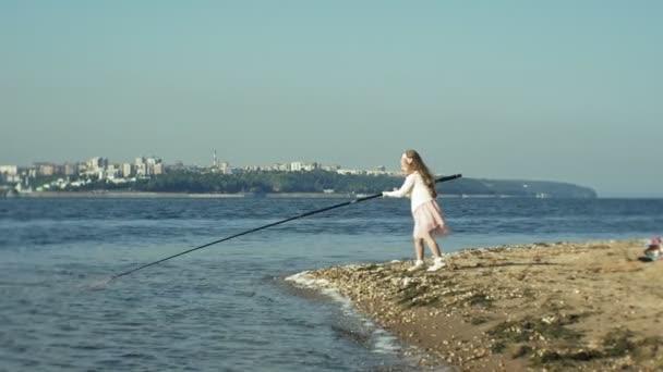 Aranyos kis lány játszik egy horgászbot egy csónak, a folyó közelében