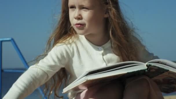 Sladká dívka sedí na písku a čte knihu tahy pes