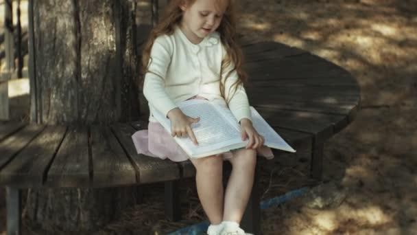 Sladká dívka sedí v lese a čte knihu