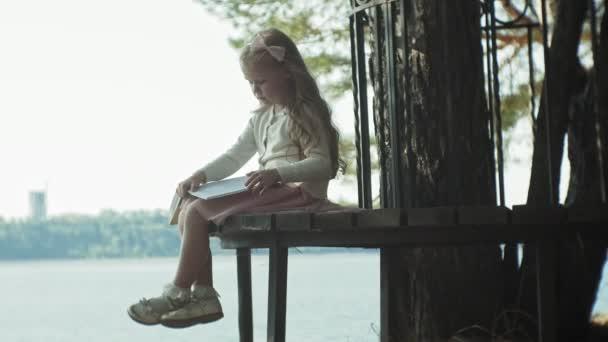 Sladká dívka sedí v lese a čte knihu 4k