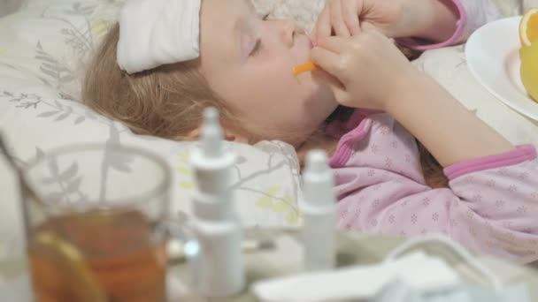 Sick girl with fever. A child with fever lies in bed and eats fruit.