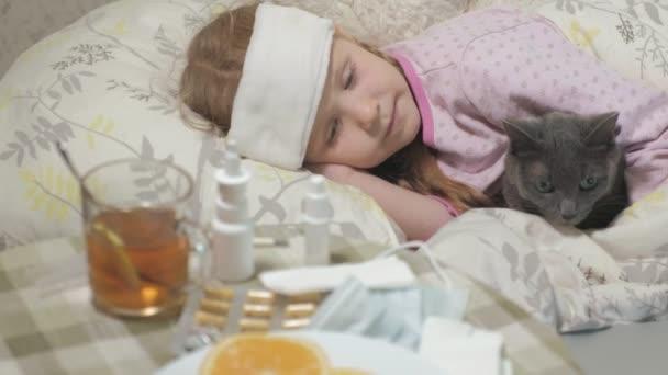 krankes Mädchen mit einer Temperatur. ein Kind mit Fieber liegt mit einer Katze im Bett.
