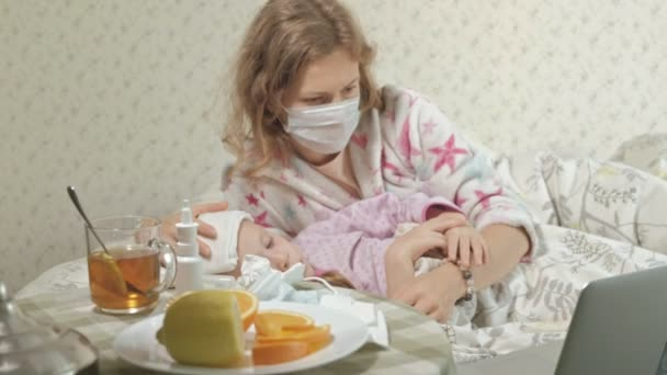 Sick girl with a temperature. Child with fever is lying in bed with her mother, eating fruit and using a laptop.