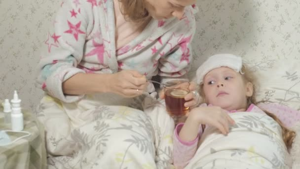 Sick girl with fever. Child with fever: a woman caring for a child and medicating