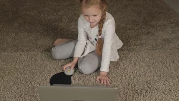 Šťastná holčička doma pracuje s notebookem