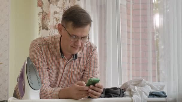 A man strokes his shirt on the ironing board in his house and uses a smartphone