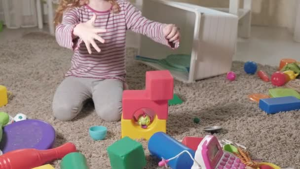 Lovely laughing little kid, preschool blonde, playing with colorful toys, sitting on the floor in the room