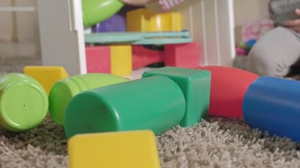 Szép nevető kis gyerek, iskoláskor előtti szőke, játék a színes játék, a fehér doboz, ült a földön, a szobában