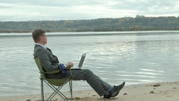 Mature businessman sitting and relaxing near a river. Man in suit and using laptop. 4k