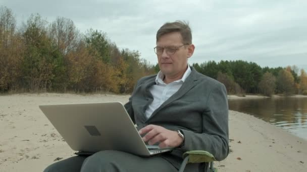 Mature businessman sitting and relaxing near a river. Man in suit and using laptop.