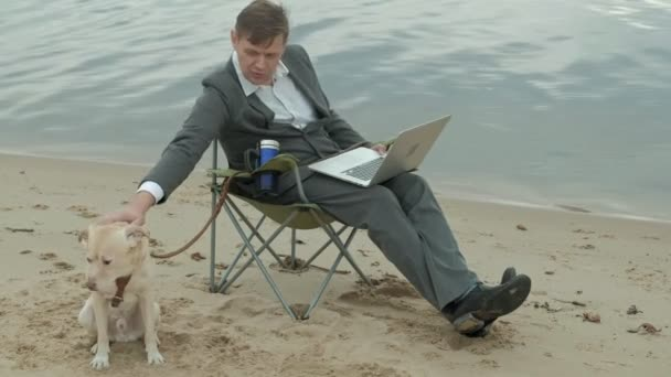 Mature businessman with dog sitting and relaxing near a river. Man in suit and using laptop.