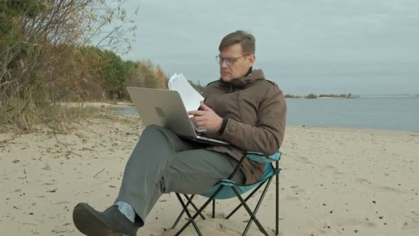 Mature businessman sitting and relaxing near a river. Man in a warm jacket and using laptop.