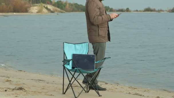 Mature businessman sitting and relaxing near a river. Man in a warm jacket and using a smartphone.