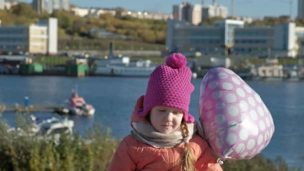 Little girl in a pink hat with a balloon sitting on the river port, traveling, smiling