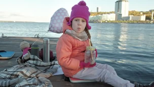 little girl, in warm clothes, sits on the bank of the river, on the river port, drinks hot tea, picnic