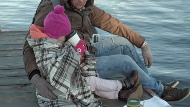man and girl, father and daughter, sit in the river port, drink tea, picnic, laugh, in warm clothes