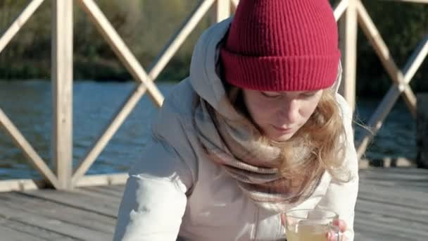 Woman tourist in warm clothes on the bridge by the river bank with a backpack, drinking hot tea, picnic, active rest, healthy lifestyle. Travel concept