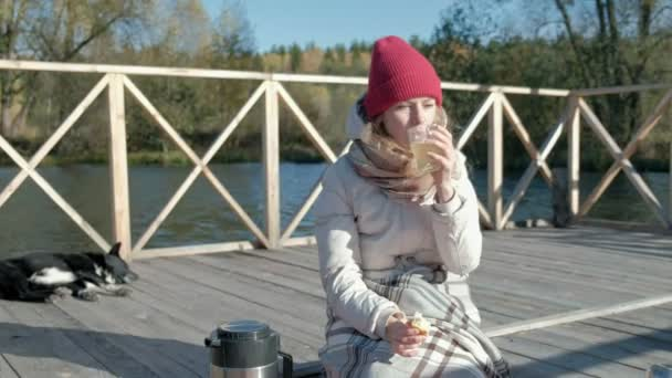 A woman tourist in warm clothes on a bridge near the river bank with a backpack, drinking hot tea, a picnic, a dog lying next to her, active leisure, healthy lifestyle. Travel concept