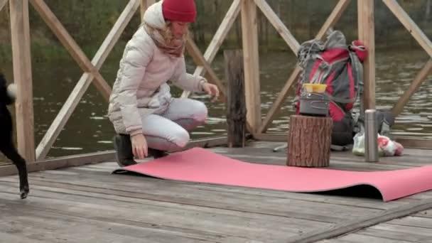 Žena turistické na mostě poblíž břehu řeky bere věci mimo její batoh, šíří turistické koberec, běží pes, piknik, outdoorových aktivit a o. cestovní koncept zdravého životního stylu