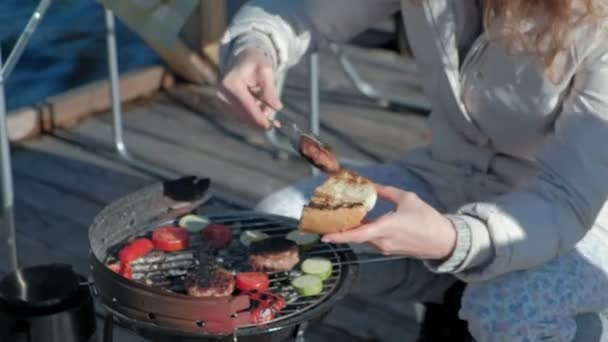 young woman in warm clothes, preparing vegetables and meat on the grill, preparing a burger, a dog playing nearby, a picnic on the river bank on a wooden bridge, a weekend, cold weather, outdoor