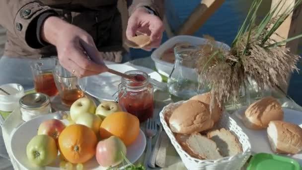 Pánské ruce dát džem na palačinky, piknik u řeky na dřevěný most, víkend, chladné počasí, camping, Turistika
