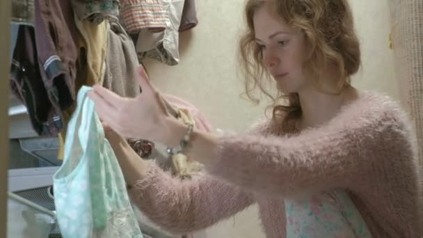 A beautiful girl smiles, sorts and folds the clothes in the baskets in her dressing room. puts things in order