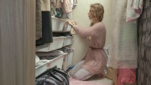 A beautiful girl, a young mother picks up and folds childrens clothes in baskets in her dressing room. puts things in order