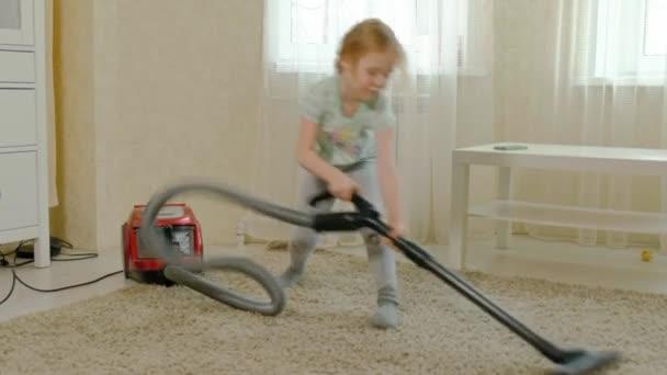 ein kleines Mädchen mit blonden Haaren räumt mit einem Staubsauger auf, bringt Ordnung und Sauberkeit, hilft Mama 4k