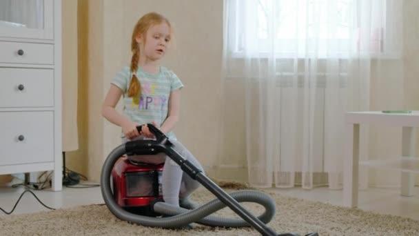 ein kleines Mädchen mit blonden Haaren sitzt auf einem Staubsauger und räumt auf, bringt Ordnung und Sauberkeit, hilft Mama 4k