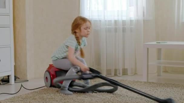 ein kleines Mädchen mit blonden Haaren sitzt auf einem Staubsauger und räumt auf, bringt Ordnung und Sauberkeit, hilft Mama