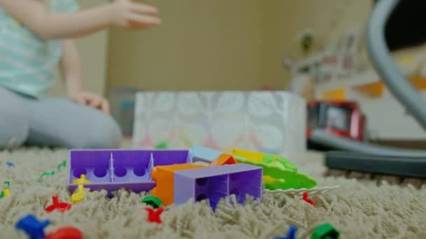 Mutter und Tochter, eine junge Frau räumt mit einem Staubsauger auf, ein kleines Mädchen mit blonden Haaren sammelt Spielzeug, die Designerin im Container, hilft Mama, aus nächster Nähe