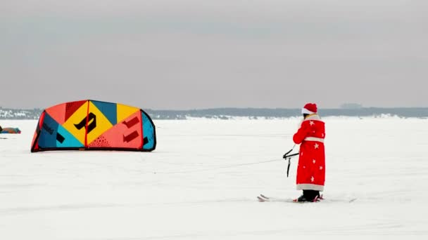 CHEBOKSARY, RUSSIA - DECEMBER 31, 2018: Snowkiting athlete, in the winter in a suit of Santa Clauss, lifts the parachute into the sky