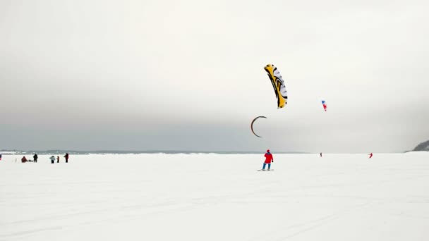 CHEBOKSARY, RUSSIA - DECEMBER 31, 2018: snowkiting athletes ride on the river in Santa Claus costumes in winter
