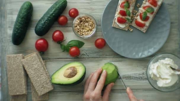 Female hands slicing avocado for sandwich. Healthy vegetarian sandwiches, kitchen table with various vegetables and greens. Cooking background, top view