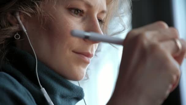 Atraktivní mladá žena s tabletem v kavárně, na volné noze koncepce